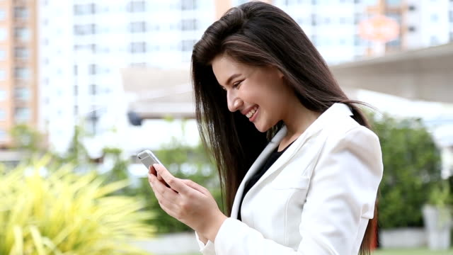 vidéos et rushes de heureuse jeune femme à l'aide de téléphone portable. - enthousiaste