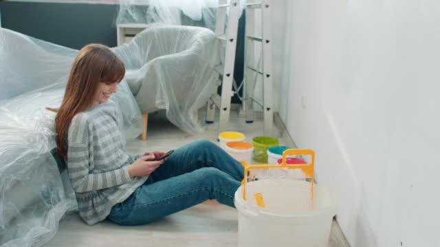 自宅で壁を塗装しながら電話を使用して幸せな若い女性 - 日曜大工点の映像素材/bロール