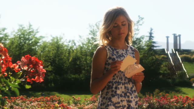 vídeos de stock, filmes e b-roll de slo mo ms pan happy young woman walking through summer garden and reading letter, lehi, utah, usa - lehi