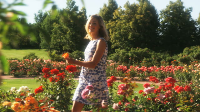 vídeos de stock, filmes e b-roll de slo mo ms pan happy young woman walking through summer garden, lehi, utah, usa - lehi
