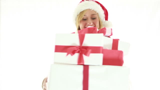Happy young woman wearing christmas hat and holding presents