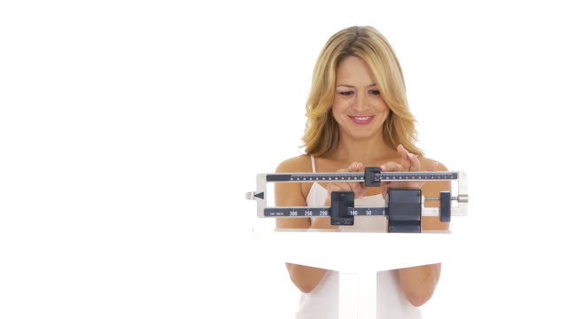 Happy young woman weighing herself on scale
