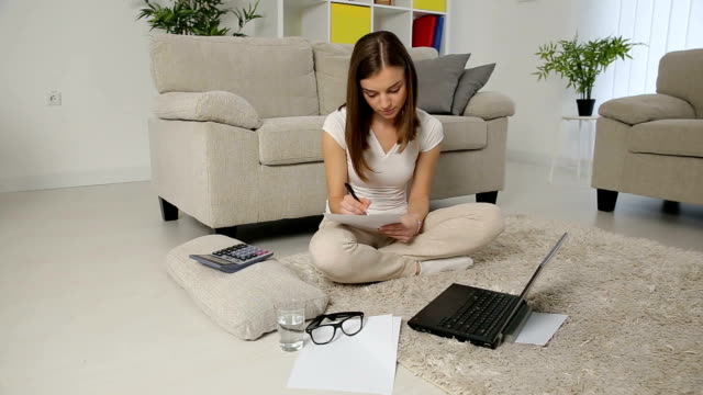 Happy young woman working with financial data from home