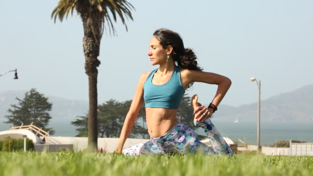 A happy young women practicing yoga outdoors on a sunny day near a body of water.