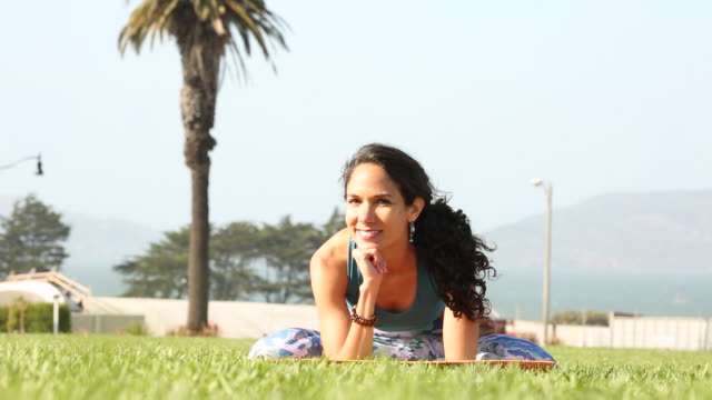 a happy young women practicing yoga outdoors on a sunny day near a body of water. - sunny video stock e b–roll