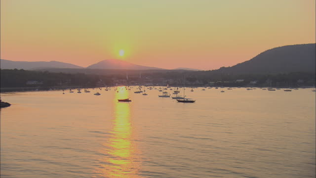 low aerial, harbor and lighthouse at sunset, camden, maine, usa - rockport maine stock videos & royalty-free footage