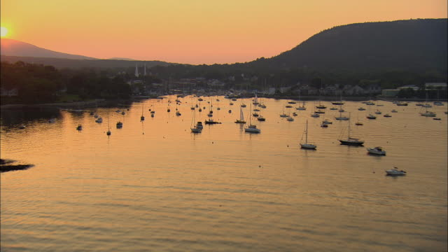 low aerial, harbor and town at sunset, camden, maine, usa - rockport maine stock videos & royalty-free footage