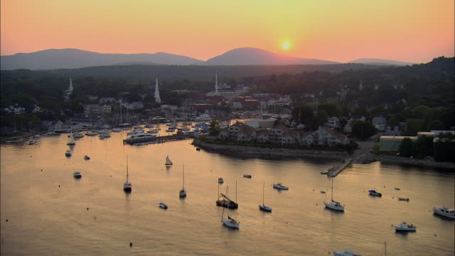 LOW AERIAL, Harbor and town at sunset, Camden, Maine, USA