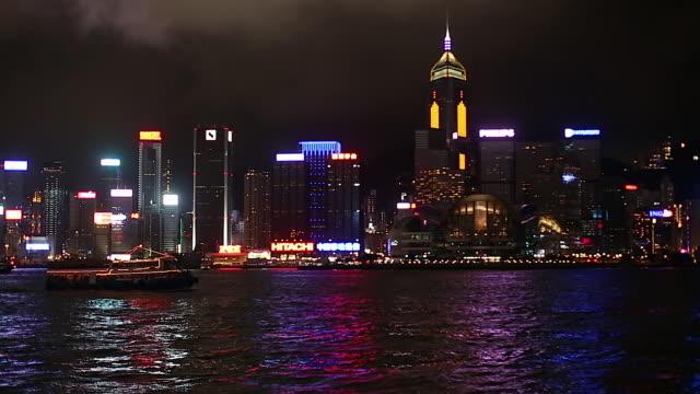 ws pan harbor ferries at night / hong kong, china - トラッキングショット点の映像素材/bロール