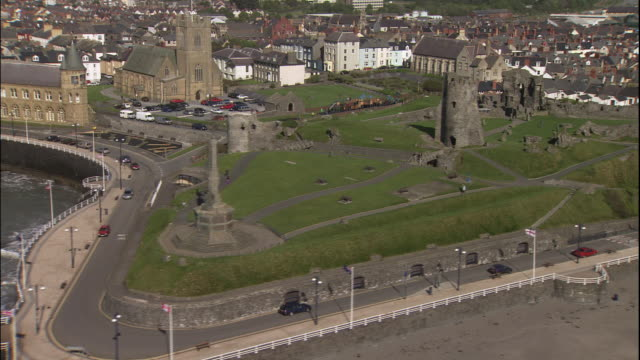 a harbor lies beyond castle ruins and a monument in aberystwyth, wales. - aberystwyth stock videos & royalty-free footage