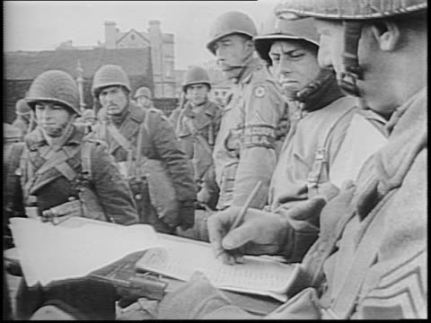 harbor with landing barges ships barrage balloons in air / troops with packs boarding ships / officer checks off names from list as soldiers pass /... - アロマンシェス点の映像素材/bロール
