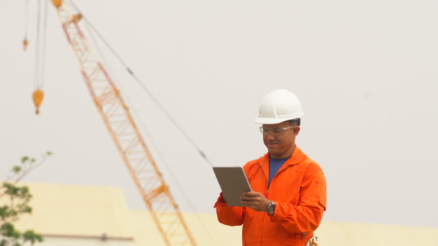 harbor worker in orange uniform is using digital tablet on cargo harbor site - loading stock videos & royalty-free footage
