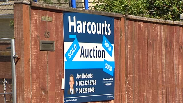 harcourts real estate auction sign with sold stickers on fence outside property - real estate sign stock videos & royalty-free footage