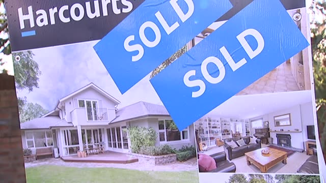 Harcourts real estate sign with 'sold' stickers outside property