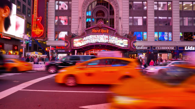 vídeos de stock e filmes b-roll de hard rock cafe big street sign and entrance. other retail stores and shops, like lids and starbucks. cafes, restaurants. yellow taxis travel on the road. advertisement billboards. times square, new york, us - locais geográficos