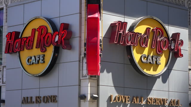 hard rock cafe is a chain of theme restaurants this one is a tourist attraction located in the busiest intersection in the city - hard rock cafe stock videos & royalty-free footage