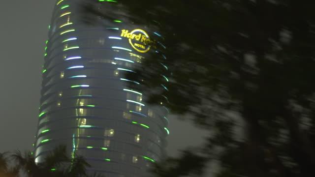 hard rock hotel tower, skyscraper, trees fg, cloudy dark sky, fog, smog bg. - macao stock videos & royalty-free footage