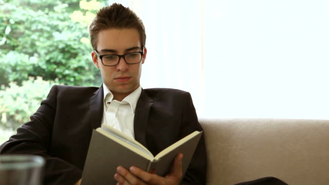 Hardback book, Young man reading at home.