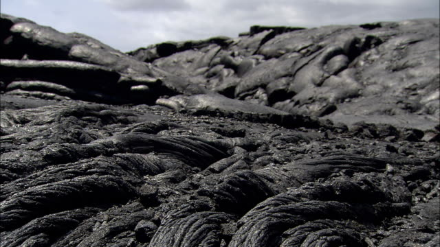 hardened lava weaves strands along a hillside. - solid stock videos & royalty-free footage