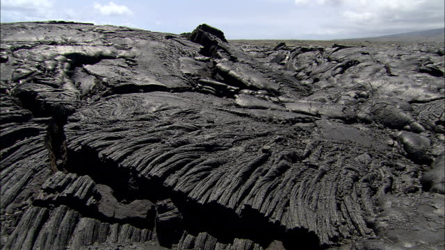 vídeos de stock, filmes e b-roll de hardened lava weaves strands along a hillside. - geologia