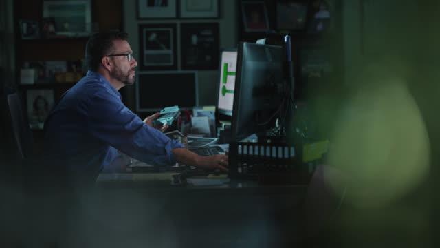 hard-working businessman studies computer screen in dark office - data stock videos & royalty-free footage