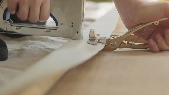 cu hardworking individual staples material to wood with utility tools - ホッチキス点の映像素材/bロール