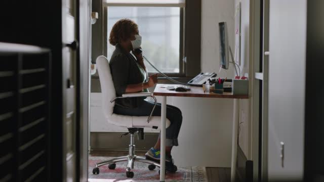 hard-working office employee wearing face mask uses landline phone at computer desk in office - landline phone stock videos & royalty-free footage