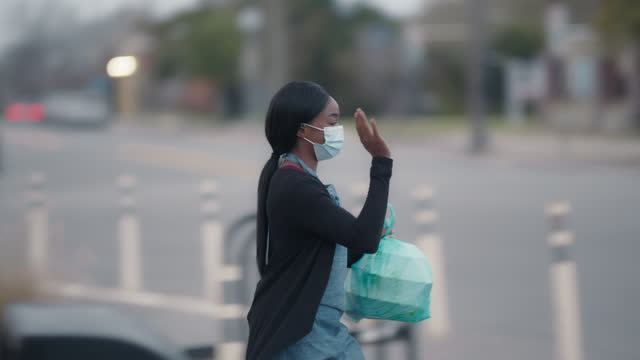 hard-working woman wearing a mask brings takeout order to a car - restaurant stock videos & royalty-free footage
