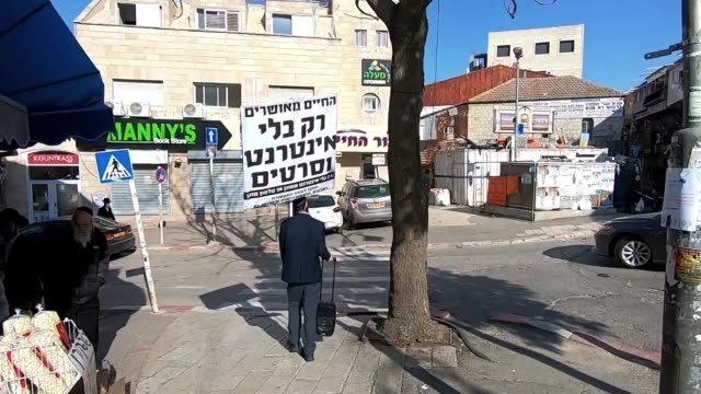 vídeos de stock, filmes e b-roll de haredi jew walking with a portable loudspeaker streaming messages about the dangers of the internet in mea shearim neighborhood, an ultra-orthodox... - portable information device