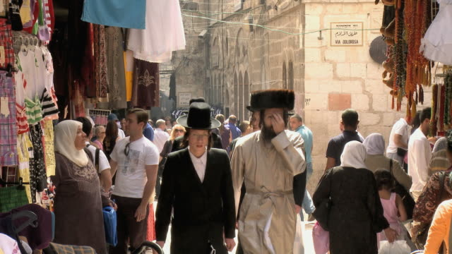 ms haredi jewish men walking through old city street / jerusalem, israel - ヴィアドロローサ点の映像素材/bロール