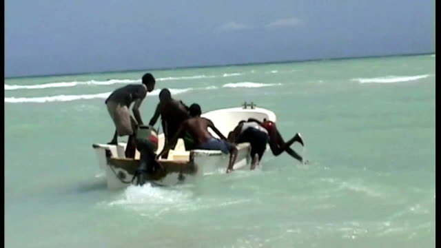 Hargeisa EXT Group of young Somali pirates pushing small boat into waves from beach as setting out on piracy raid Young pirates seated in boat with...
