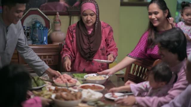 vidéos et rushes de hari raya grand-mère malaise, fils et belle-fille servant de la nourriture à la famille à la salle à manger - invité