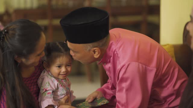 hari raya malay muslim baby girl in traditional clothing receives a money packet on hari raya aidilfitri / eid-ul-fitr celebration in living room - malaysian culture stock videos & royalty-free footage