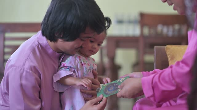 hari raya malay muslim baby girl in traditional costume receives a money packet on hari raya aidilfitri / eid-ul-fitr  celebration in living room - malaysian culture stock videos & royalty-free footage