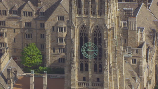 MS TU HA POV Harkness Tower with clock and sculpture on the Yale University campus / New Haven, Connecticut, United States