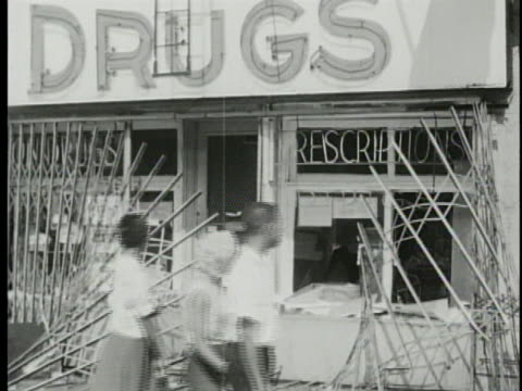 vídeos de stock e filmes b-roll de harlem drugstore shows damage after being looted during a riot. - 1964