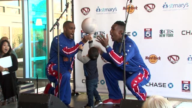 harlem globe trotters and audience member at nick cannon rocks lights empire state building for st. mary's kids at the empire state building on... - ハーレムグローブトロッターズ点の映像素材/bロール
