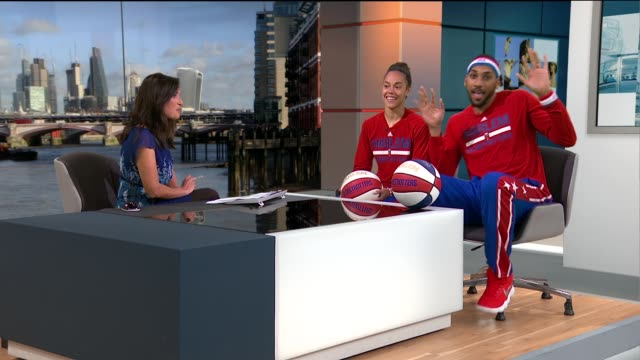 harlem globetrotters come to london; england: london: gir: int hoops green and zeus mcclurkin set up shot reporter to camera - ハーレムグローブトロッターズ点の映像素材/bロール