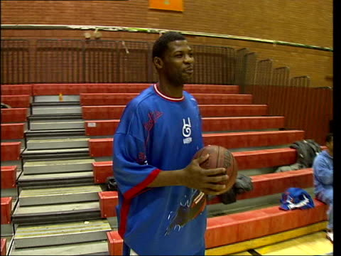 london brixton int curley 'boo' johnson bouncing two basketballs inside sports hall alex big ticket sanders jumping and putting basketball through... - harlem globetrotters stock videos & royalty-free footage