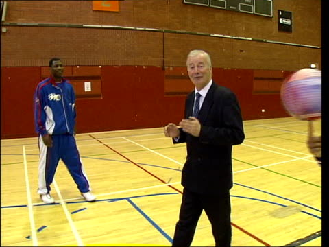 harlem globetrotters; itn london: brixton: curley 'boo' johnson showing young schoolgirl how to spin a basketball on her finger i/c as alex sanders... - ハーレムグローブトロッターズ点の映像素材/bロール