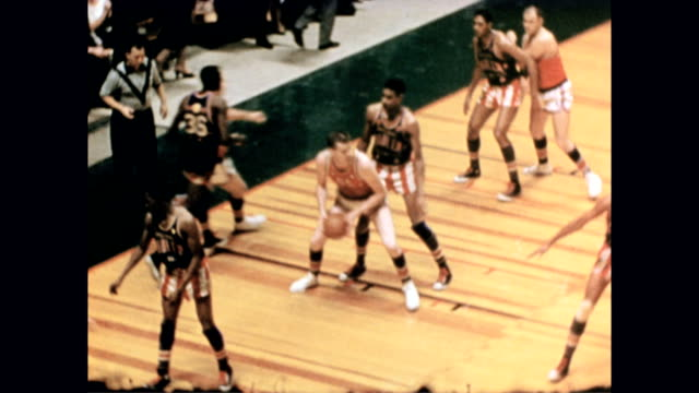 harlem globetrotters play basketball against a team of white men in red uniforms. harlem globetrotters playing basketball on january 01, 1958 - ハーレムグローブトロッターズ点の映像素材/bロール