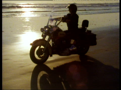 harley davidson motorcycle being ridden along a beach in golden evening light sea behind. - helmet stock videos & royalty-free footage