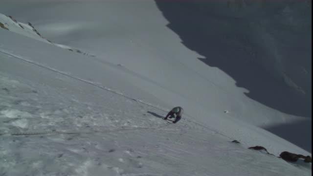 vídeos de stock e filmes b-roll de a harnessed mountain climber ascends a snowy mountain with the help of a rope. - arnês de segurança