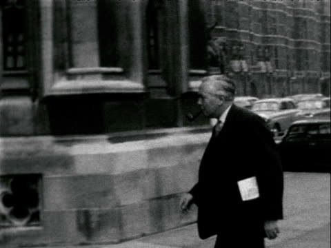 harold wilson mp passes and pauses for the camera pipe in hand before heading into houses of parliament uk 1962 - ボング点の映像素材/bロール