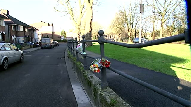 harrow woman fatally stabbed in possible row over parking space; flowers on railings alongside pavement - harrow stock videos & royalty-free footage