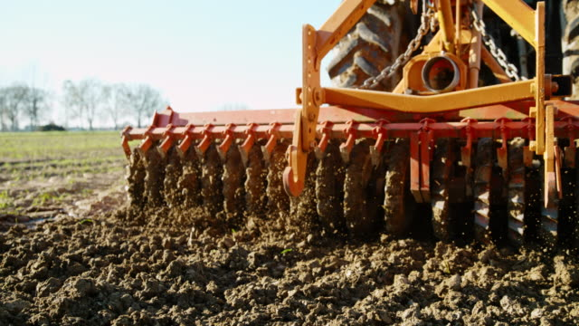 slo mo harrowing the field - agricultural machinery stock videos & royalty-free footage