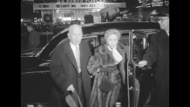 Harry Hershfield and wife in fur coat get out of limousine at NYC premiere of The Eddie Cantor Story