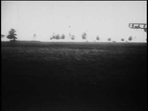 harry houdini in experimental biplane taking off from field / australia / newsreel - 1910 stock-videos und b-roll-filmmaterial