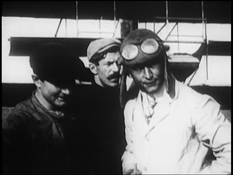 harry houdini standing in flying outfit with men / australia / newsreel - anno 1910 video stock e b–roll