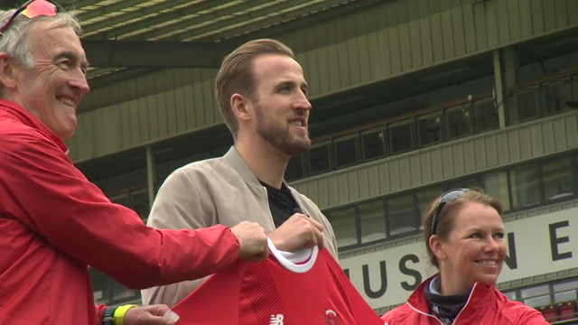 harry kane, england football captain, holding up leyton orient football shirt that he is sponsoring and then donating the space to a charity - shirt stock videos & royalty-free footage